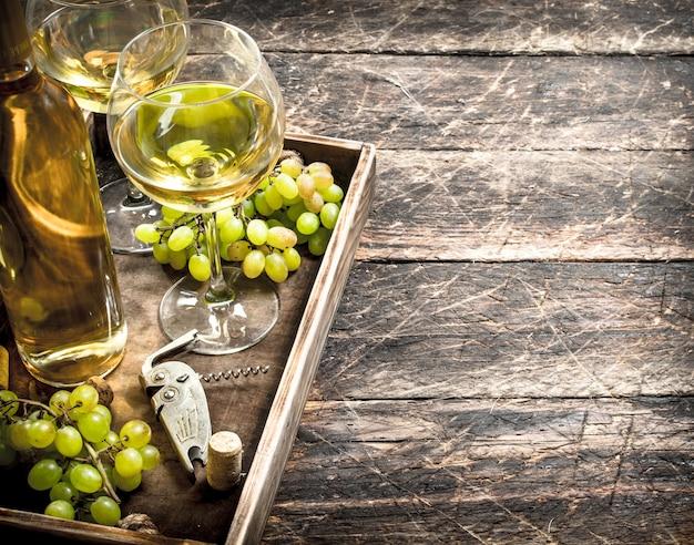 오래 된 쟁반에 신선한 포도와 화이트 와인. 나무 테이블에.
