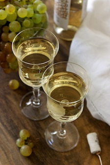 White wine with glass goblets and grape bunches