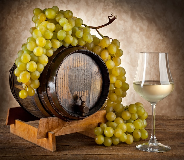 White wine with grapes and barrel