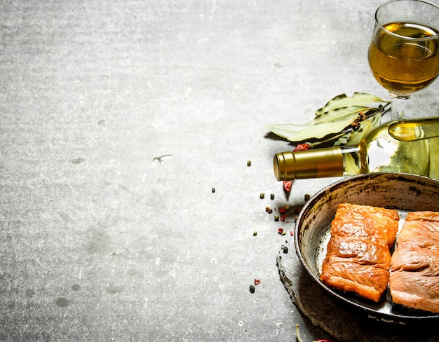 White wine with a grilled salmon fillet on the stone table.