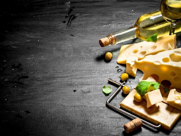 맛을 낸 치즈와 올리브 조각이있는 화이트 와인.