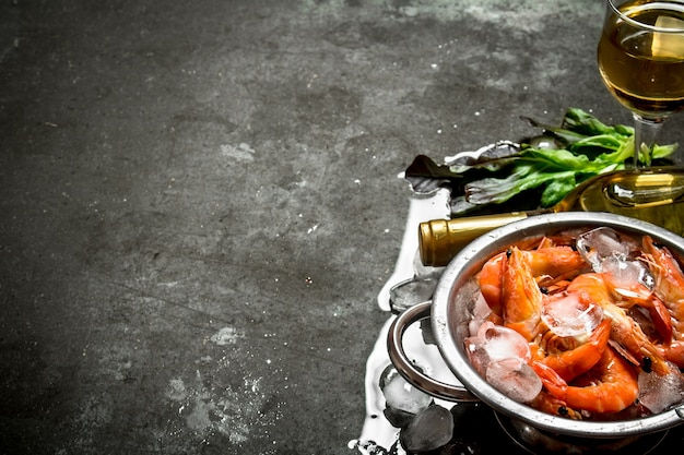 White wine with shrimp and ice on a stone background