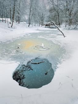 丸い背水と川の氷のある白い冬の風景。垂直方向のビュー。
