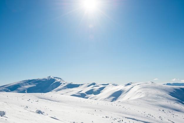 雪と明るく輝く太陽と太陽光線のある白い冬の山々
