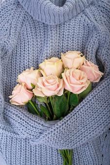 Белый зимний свитер с букетом цветов, нежных роз. весенняя и зимняя композиция настроения. плоская планировка, сверху, вид сверху.