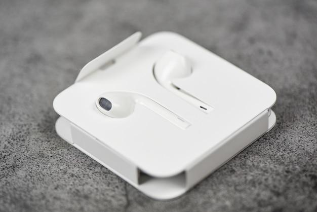 White wireless bluetooth earphones or headphones smartphone earphones in plastic storage case isolated on gary
