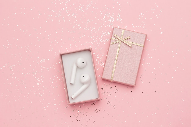 White wireless bluetooth headphones in gift box and glitter confetti on pink background