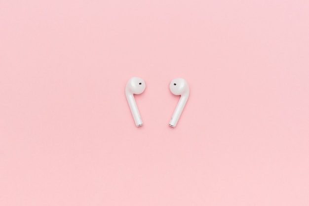 White wireless bluetooth headphones on pastel pink background