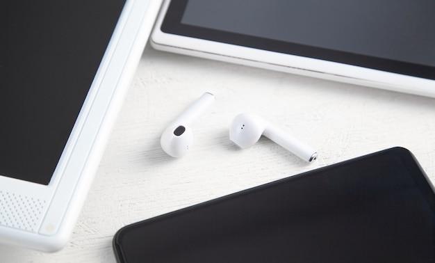 흰색 무선 이어폰, 노트북 화면, 태블릿, 스마트폰.