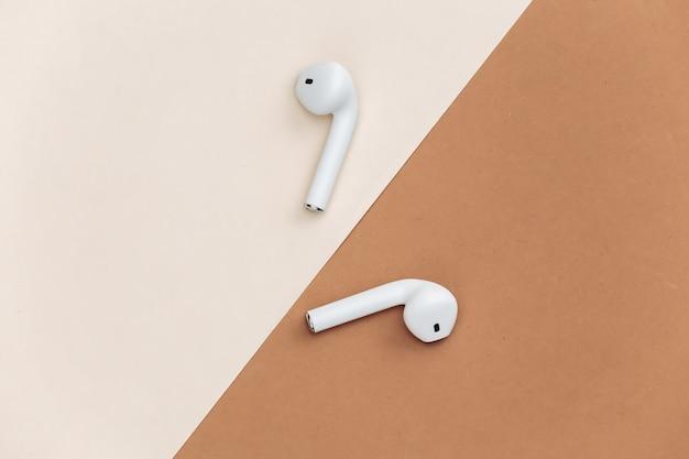 베이지색 갈색 배경에 흰색 무선 이어폰입니다.