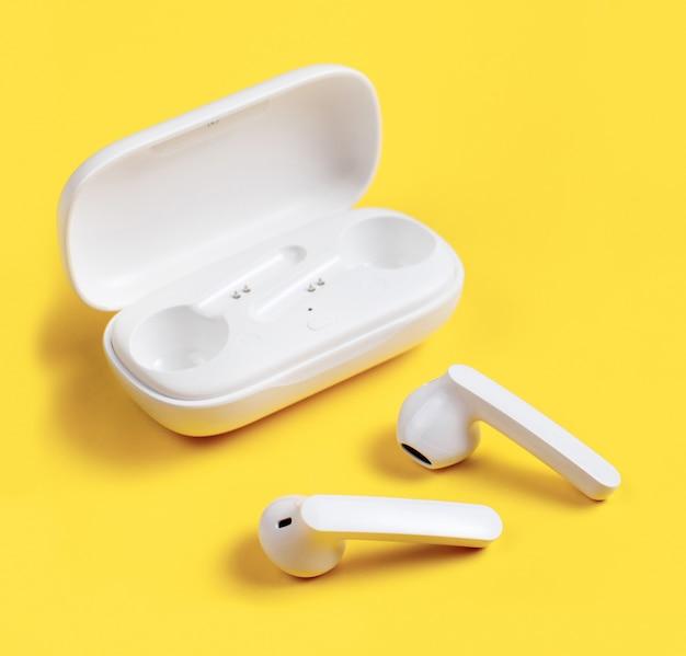 노란색 배경에 케이스와 흰색 무선 이어폰을 닫습니다.