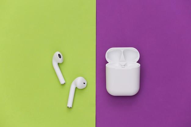 녹색 보라색 배경에 충전 케이스가 있는 흰색 무선 이어폰.
