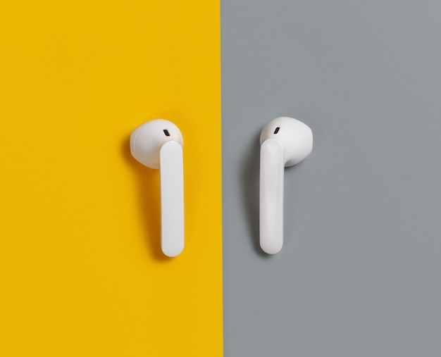 White wireless earphones on yellow and grey background  top view