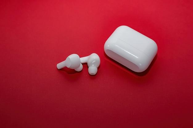 흰색 무선 헤드폰 및 충전기는 빨간색 배경에 거짓말.