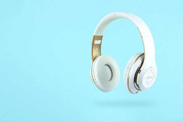 White wireless headphones on blue background. music concept.