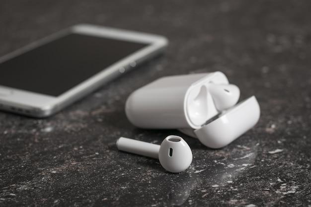 케이스에 흰색 무선 헤드폰과 돌 배경에 휴대폰. 현대적인 무선 액세서리.