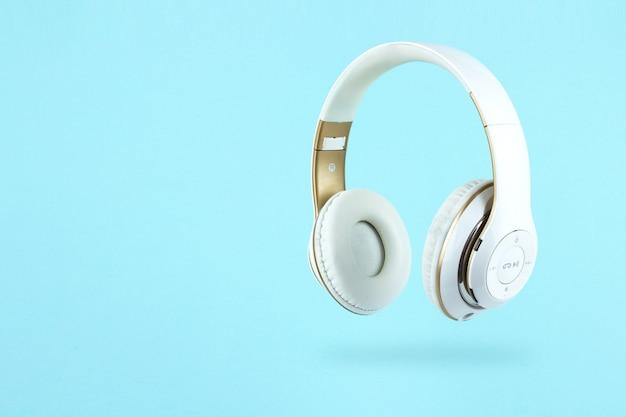 파란색 배경에 흰색 무선 헤드폰입니다. 음악 개념입니다.