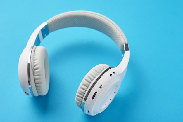 White wireless headphones on a pastel blue background