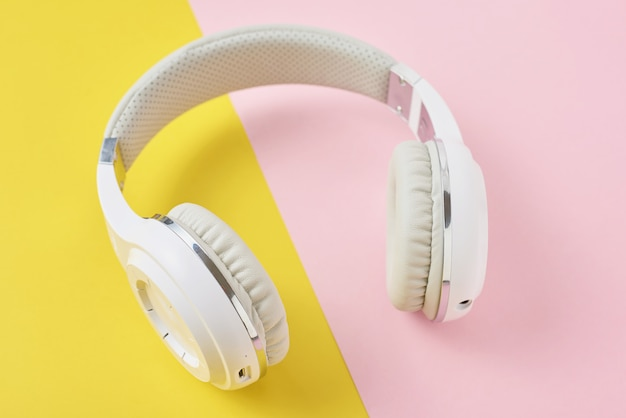 White wireless headphones on a pink and yellow background