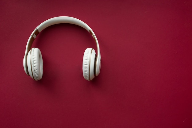 White wireless headphones on red background. top view.