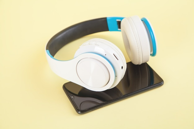 White wireless headphones and smartphone on yellow surface.