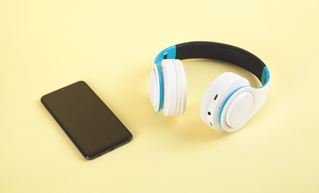 White wireless headphones and smartphone on yellow wall