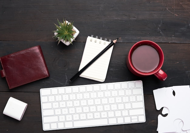 White wireless keyboard and wireless headphones and brown leather wallet on a wooden brown table, next to a white cup with coffee, top view