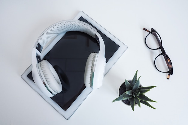 Белый беспроводной на белом планшете, очках и цветке на белом столе. уайлд на вершине. концептуальный подкаст, аудиокниги, онлайн-обучение.