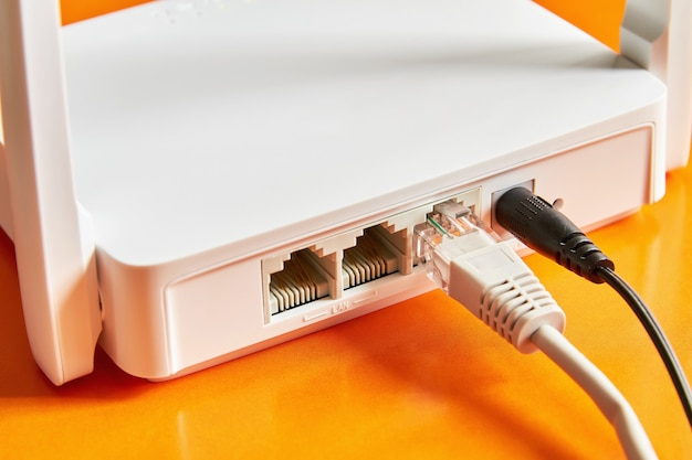 Белый беспроводной маршрутизатор на оранжевом фоне подключен по кабелю к интернету.