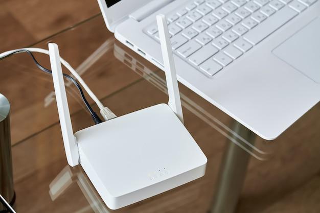유리 테이블에 노트북 근처 흰색 무선 와이파이 라우터