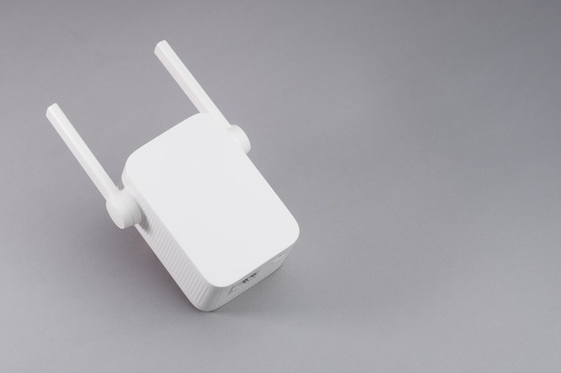 White wireless wifi repeater on gray background.