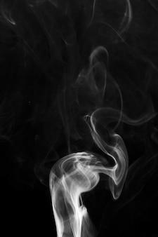 黒の背景に白のかすかな煙の渦巻き