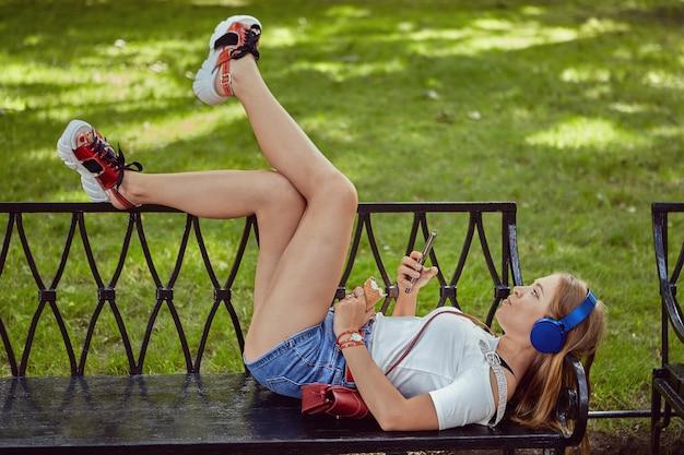 Белая женщина около 25 лет в наушниках и туфлях на платформе лежит на скамейке в общественном парке со смартфоном в руке и ест мороженое.