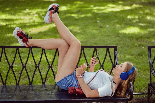 White  woman about 25 years old with earphones and platform shoes is lying on bench in public park with smartphone in hand and eating ice cream.