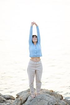 바다 앞의 돌 위에서 맨발로 스트레칭을 하는 백인 여성