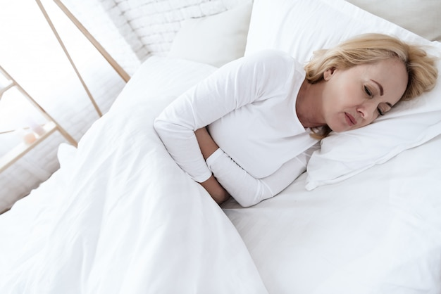 A white woman has a stomach ache lying in bed.