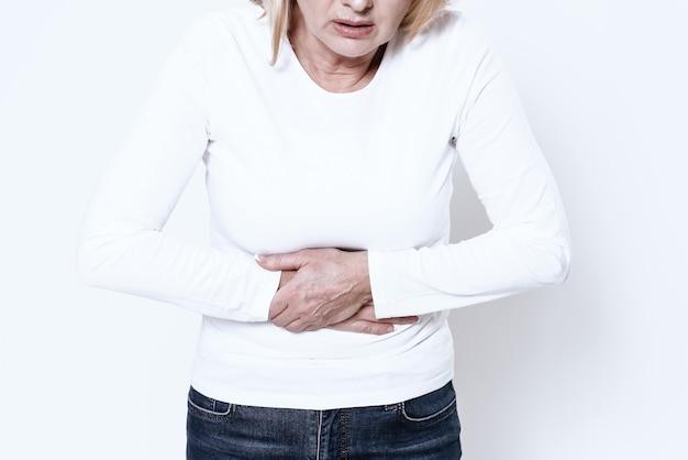 A white woman has a stomach ache in studio.