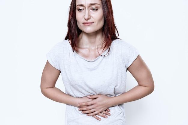 A white woman has a stomach ache.