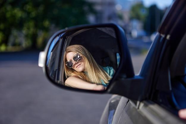 サングラスをかけた白人女性がバックミラーを見て車を運転する