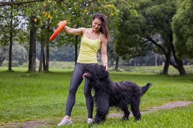 백인 여성은 공공 공원에서 걷는 동안 장난감의 도움으로 그녀의 briard를 훈련하고 있습니다.