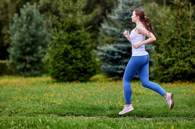 Белая женщина тренируется в парке в леггинсах