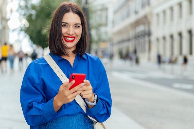 路上で携帯電話を使用しながらカメラを見ている白人女性