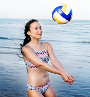 White woman playing volleyball at the beach