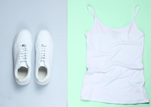Белая женская футболка, белые хипстерские кроссовки на пастельном фоне