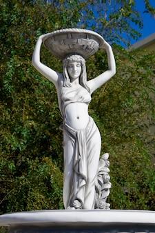 頭の上のバスケットを持つ白人女性像