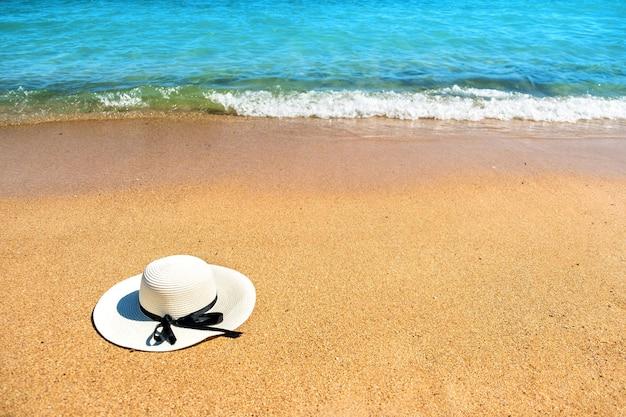 晴れた夏の日に背景に青い活気のある海の水と熱帯の砂浜に横たわる白人女性の麦わら帽子。休暇と目的地の旅行の概念。