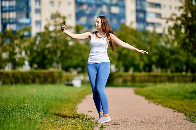 Белая женщина фотографирует по телефону в парке