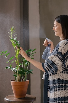 White woman watering and moisturizing flowers home plant care watering and transplanting flowers