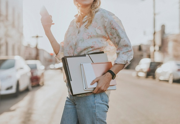 White woman with file folders crossing a street while using her phone