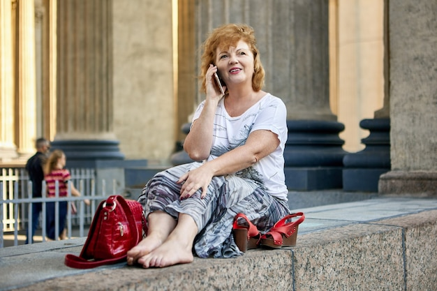 Белая женщина лет разговаривает по телефону во время прогулки по городу